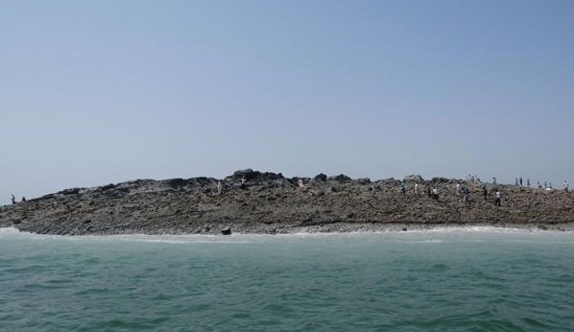 Pakistani men walk on an island that appeared off the coastline of Gwadar in this photo released by the government.